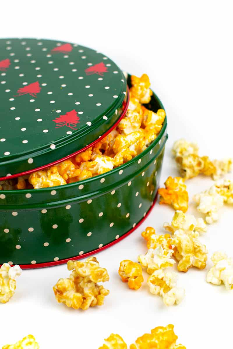 a closed tin of popcorn with popcorn overflowing on a white background