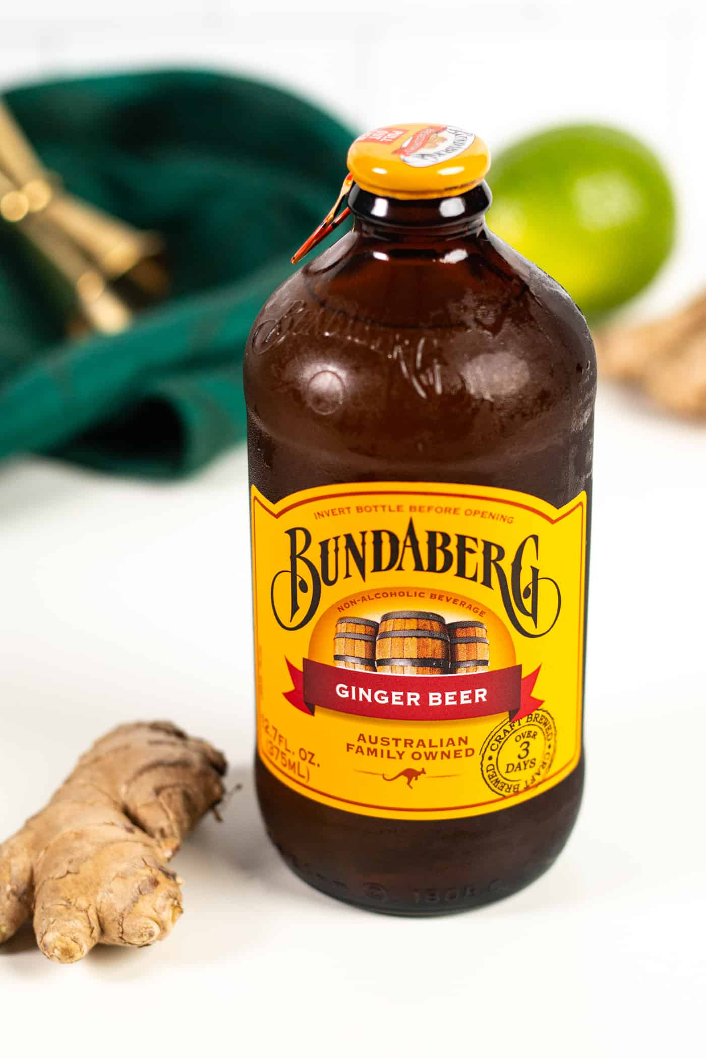 a bottle of bundaberg ginger beer with a piece of ginger root and a lime