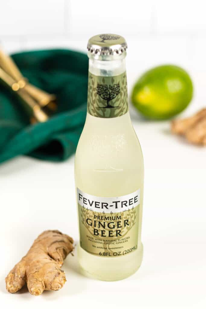 an unopened bottle of fever tree ginger beer with a piece of ginger root