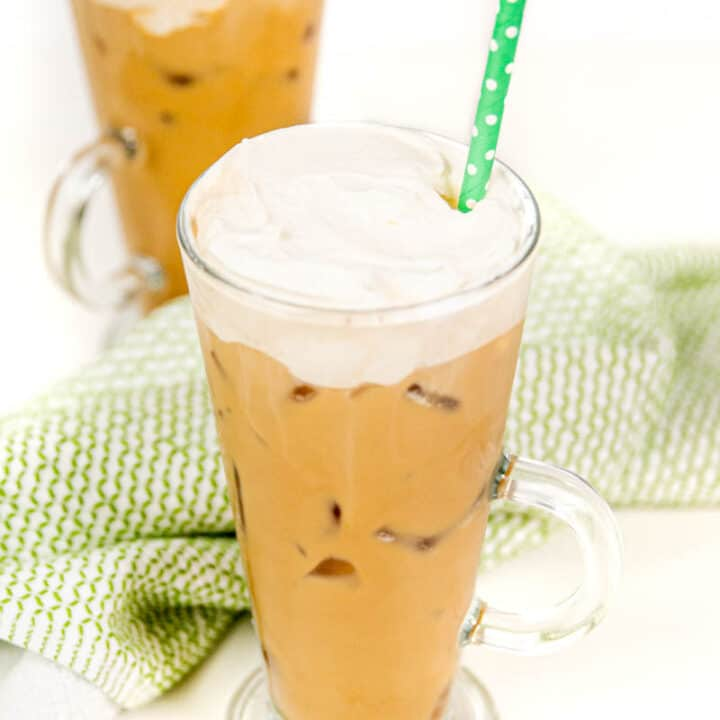 two iced irish coffee cocktails on a white background with a green tea towel