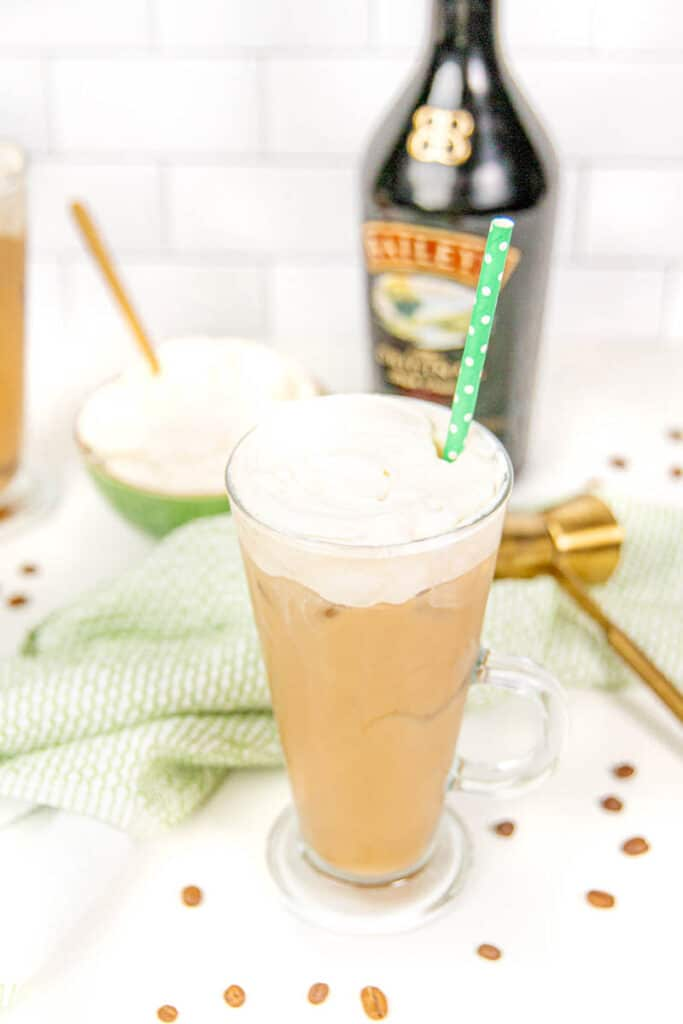 two iced irish coffee cocktails on a white background with a green tea towel and a bottle of baileys and a jigger