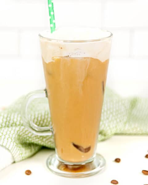an iced irish coffee cocktails with coffee beans and a green tea towel