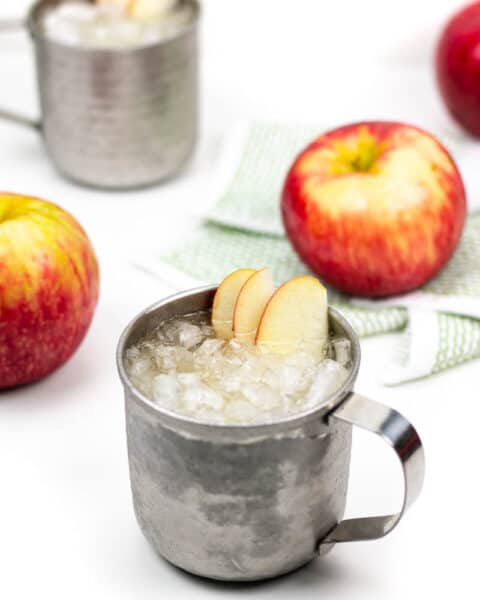 two applejack moscow mules with red apples on a white background