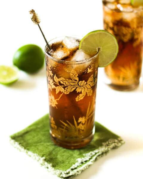 limes next to a cuba libre rum cocktail