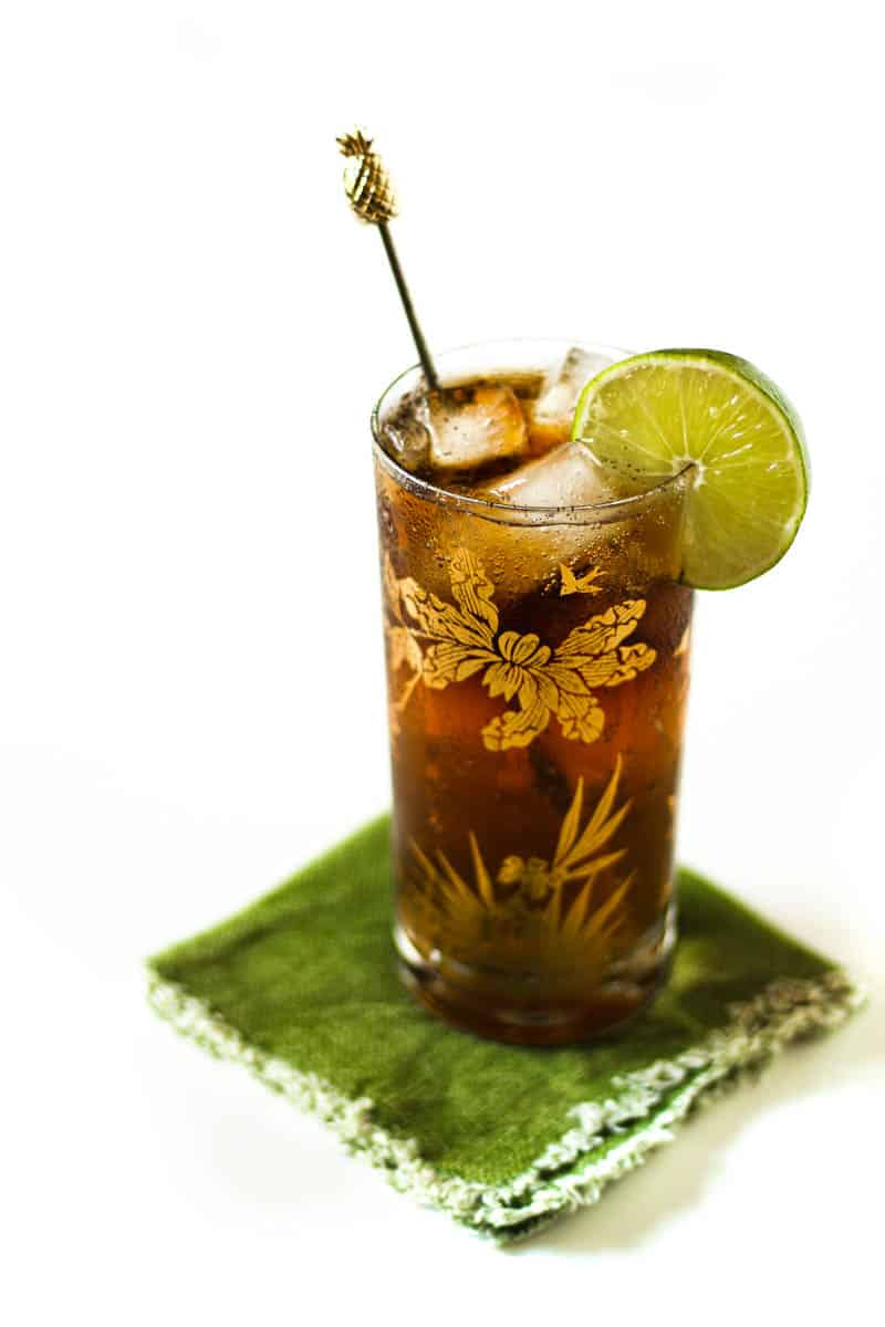 a cuba libre cocktail by itself on a green napkin against a white background