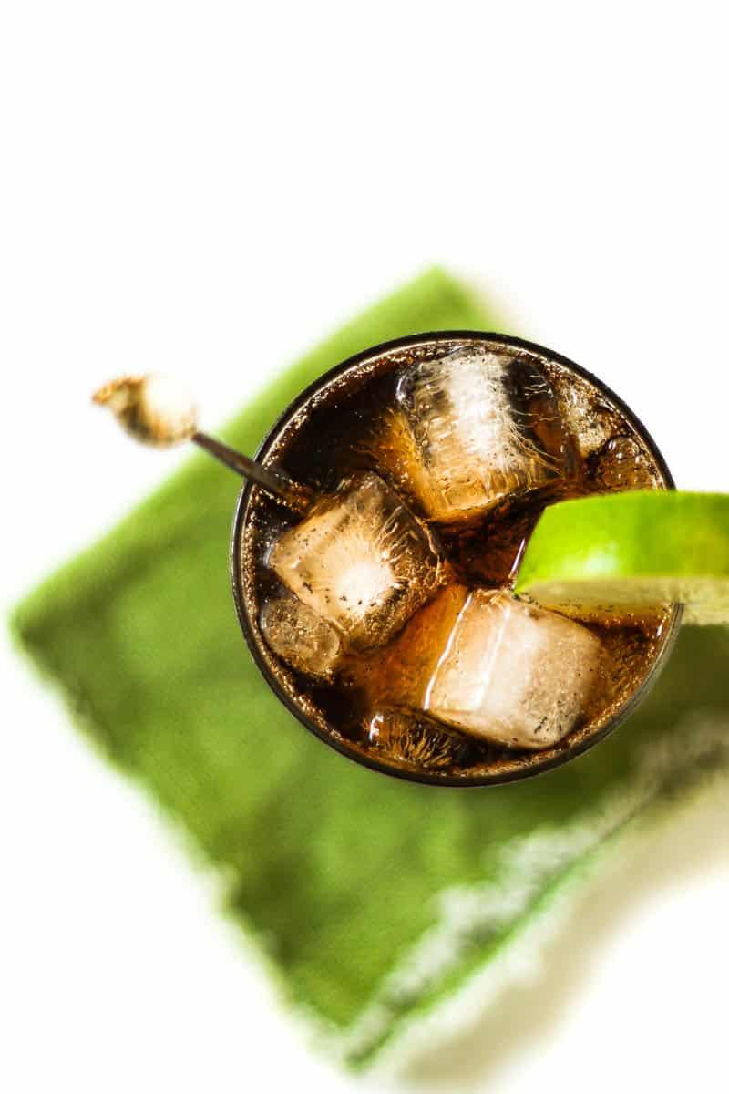 top-view of a cuba libre cocktail on a green linen napkin