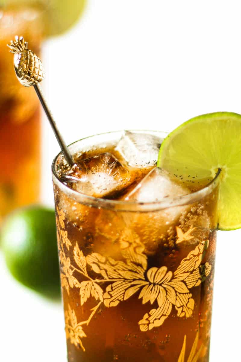 closeup of a cuba libre in a highball glass on a white background