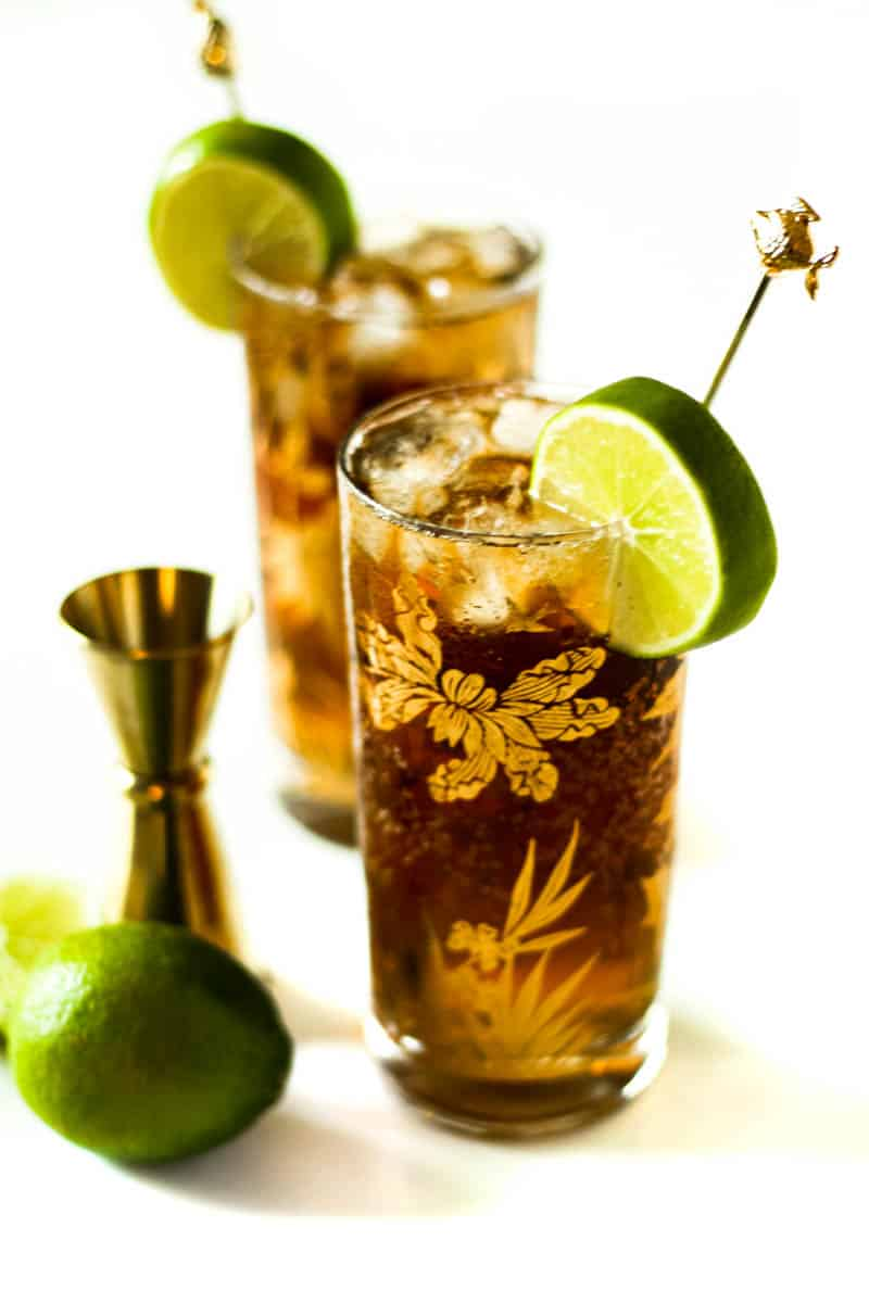 a lime, jigger and two cuba libre rum & coke cocktails