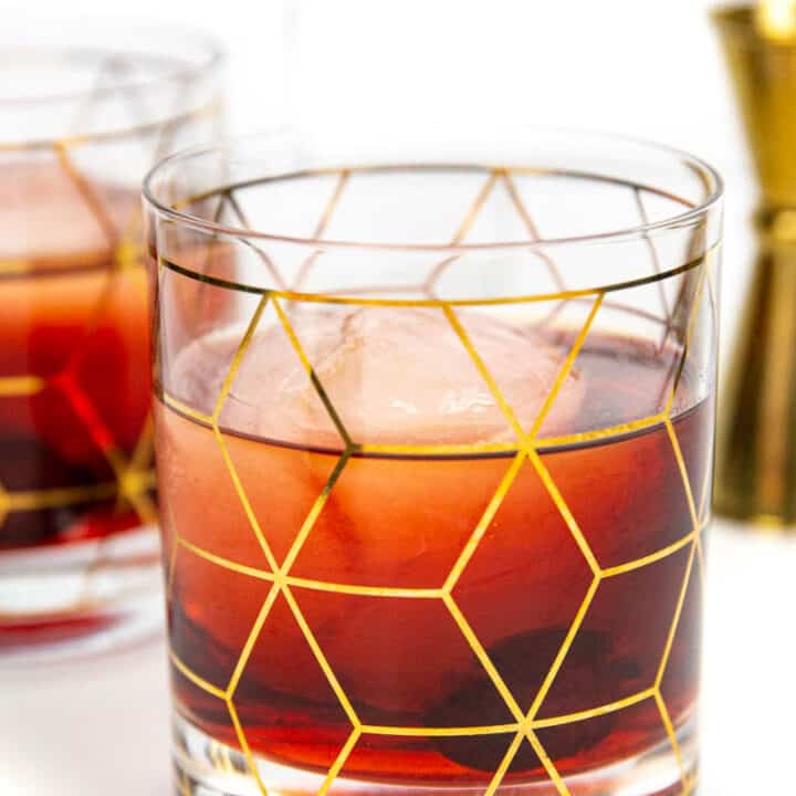 two Cheerwine Old-Fashioned with a gold jigger on a white background