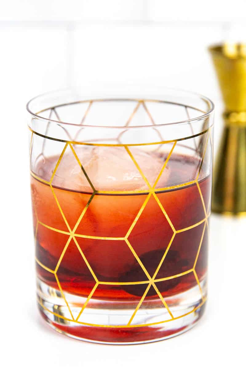 a gold jigger and a Cheerwine Old-Fashioned on a white background