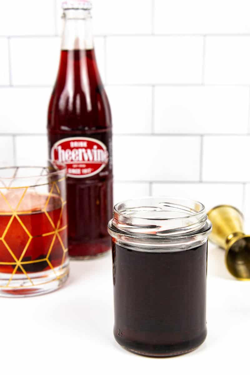 a jar of cheerwine syrup next to a jigger and a bottle of cheerwine