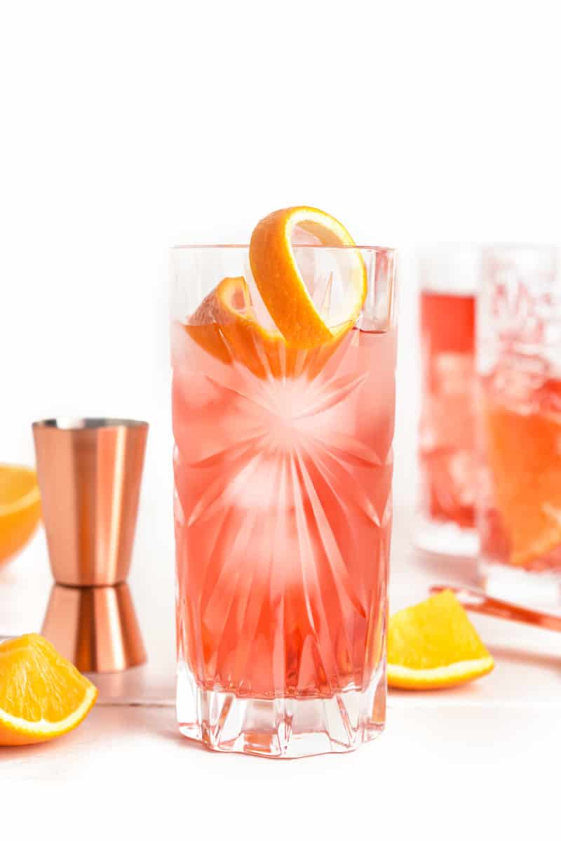 a red cocktail with an orange twist next to a copper jigger and orange slices on a white background