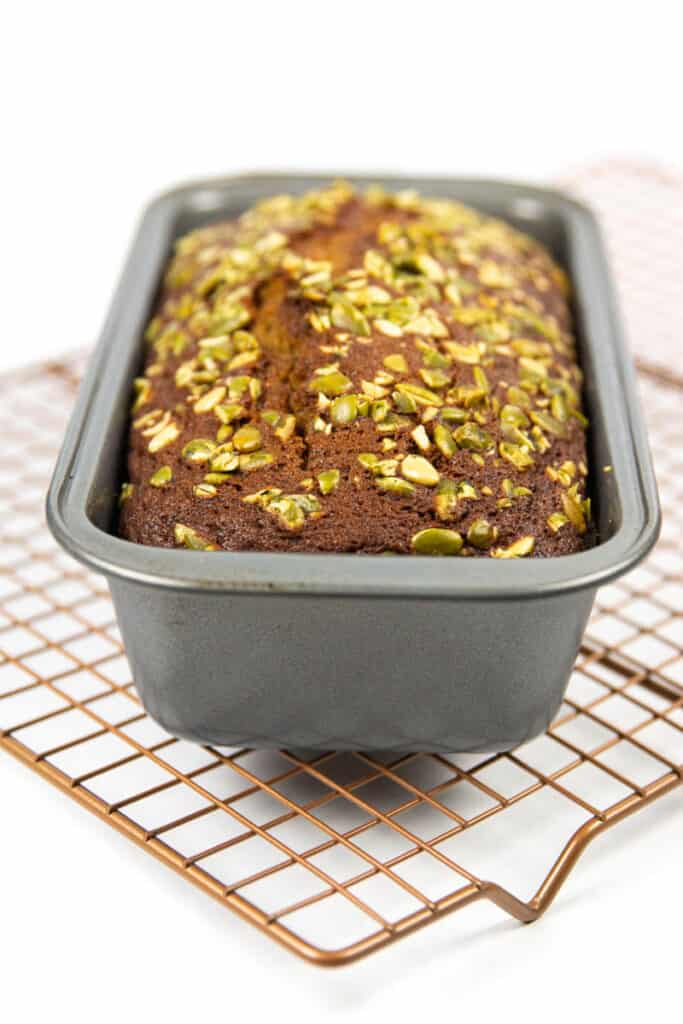 easy starbucks pumpkin bread rests in a loaf pan on a wire cooling rack