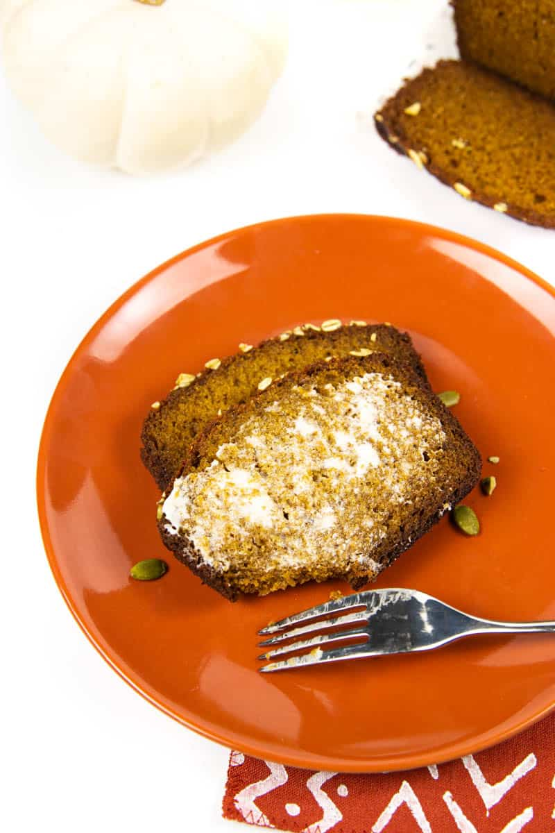 a buttered slice of pumpkin bread on an orange plate next to a loaf of pumpkin bread and two white pumpkins