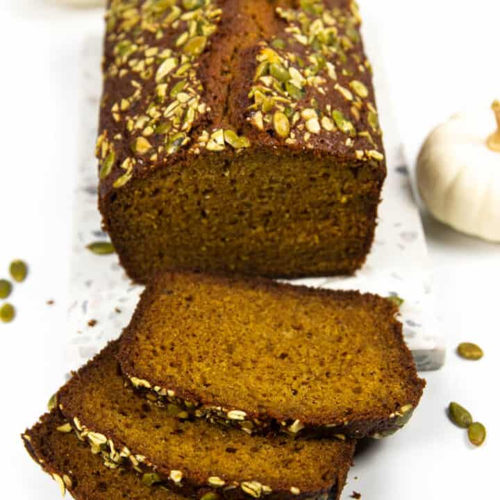 three slices of pumpkin bread lay next to a cut loaf of pumpkin bread on a terrazzo cutting board next to two white pumpkins