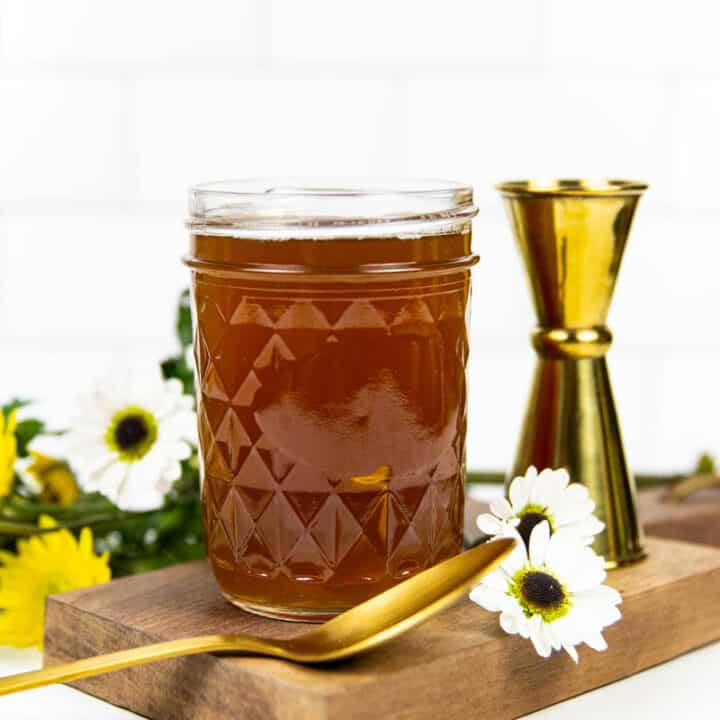 a mason jar filled with honey simple syrup next to a gold jigger and yellow and white wildflowers