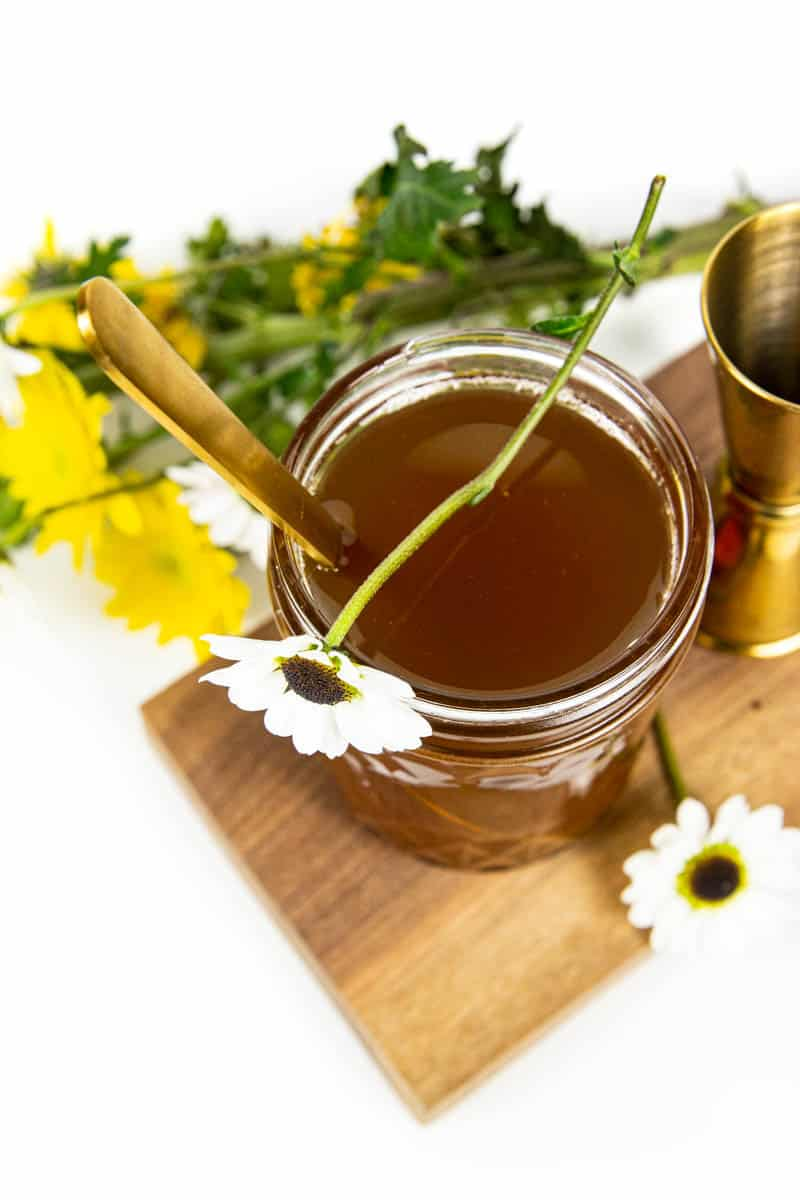 a jar of honey simple syrup on a wooden board next to a bouquet of wildflowers