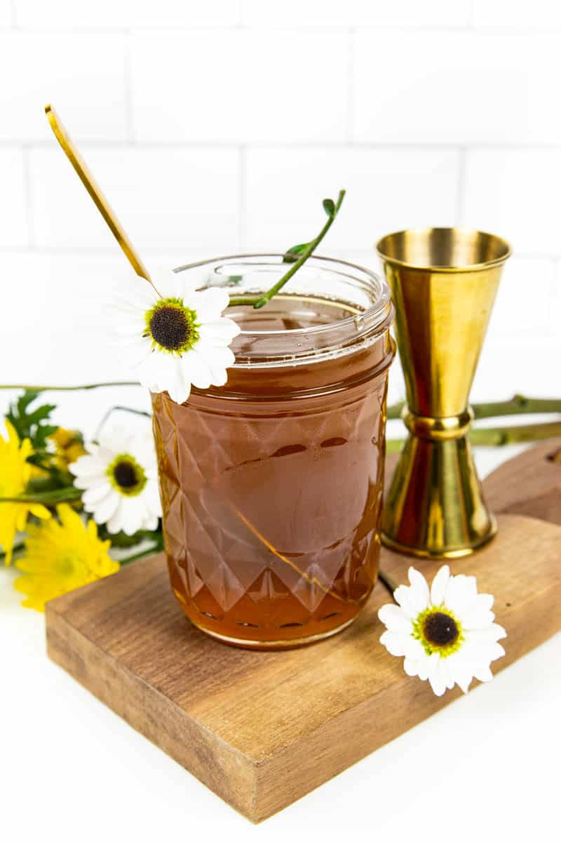 a white wildflower on top of a jar of honey simple syrup
