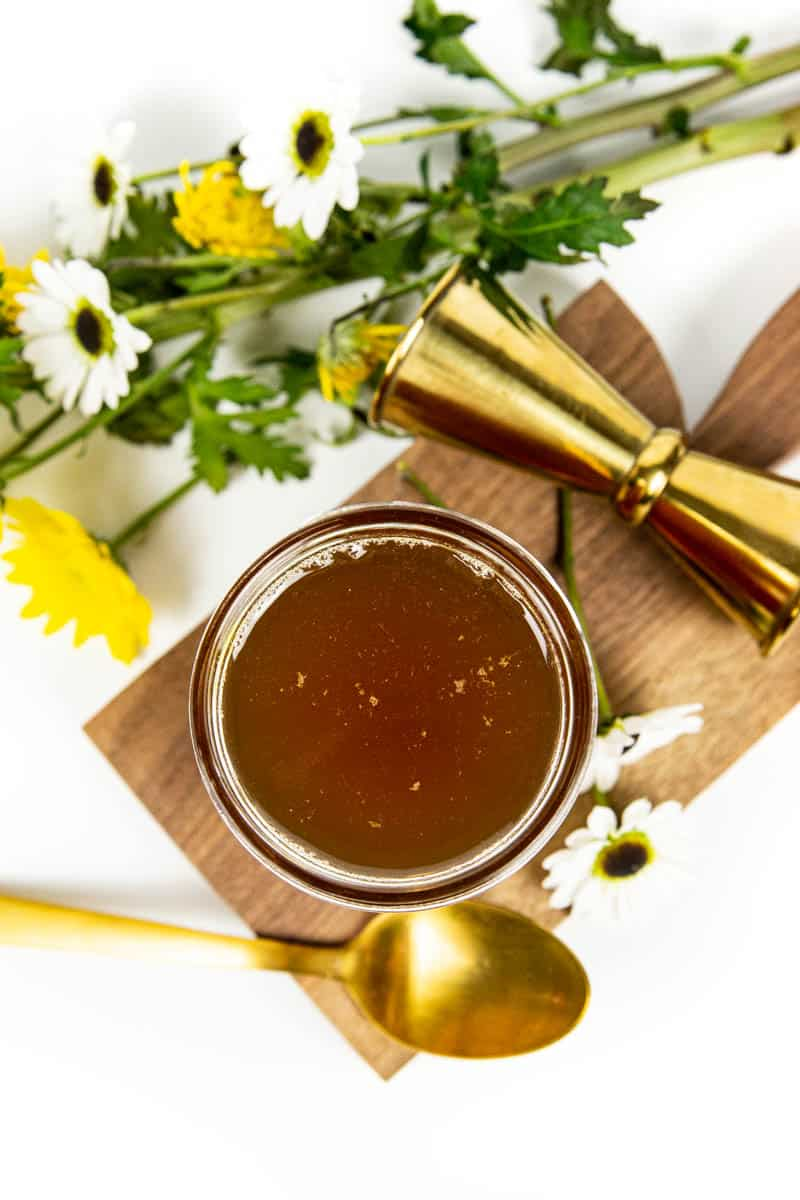 top view of a jar of honey simple syrup on a wooden board