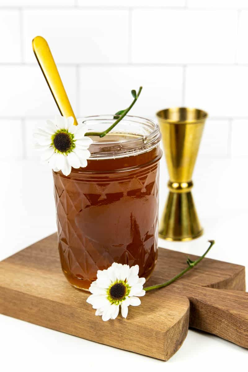 a jar of honey simple syrup sits on a wooden cutting board