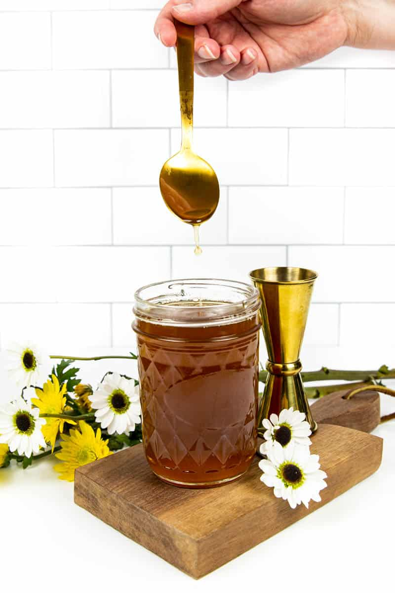 a hand holding a gold spoon drizzles honey simple syrup into a mason jar