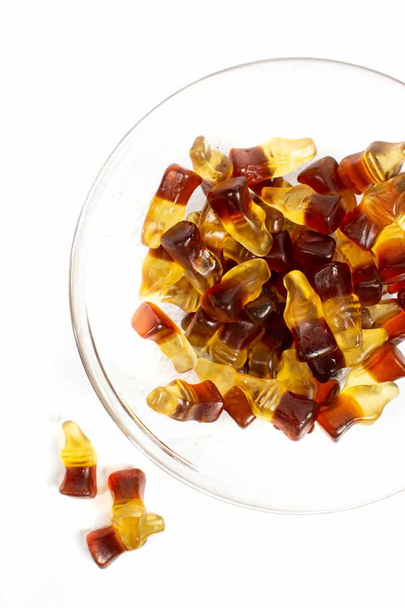 a glass bowl of jack and coke gummies on a white background
