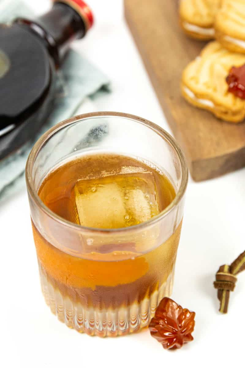 a maple old-fashioned with a maple candy with maple syrup and cookies in the background