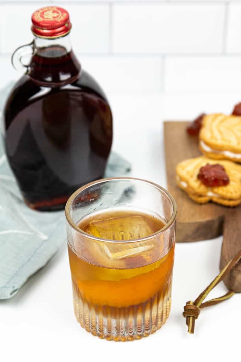 a maple old-fashioned next to a wooden platter of of maple cookies and candies and a jar of maple syrup
