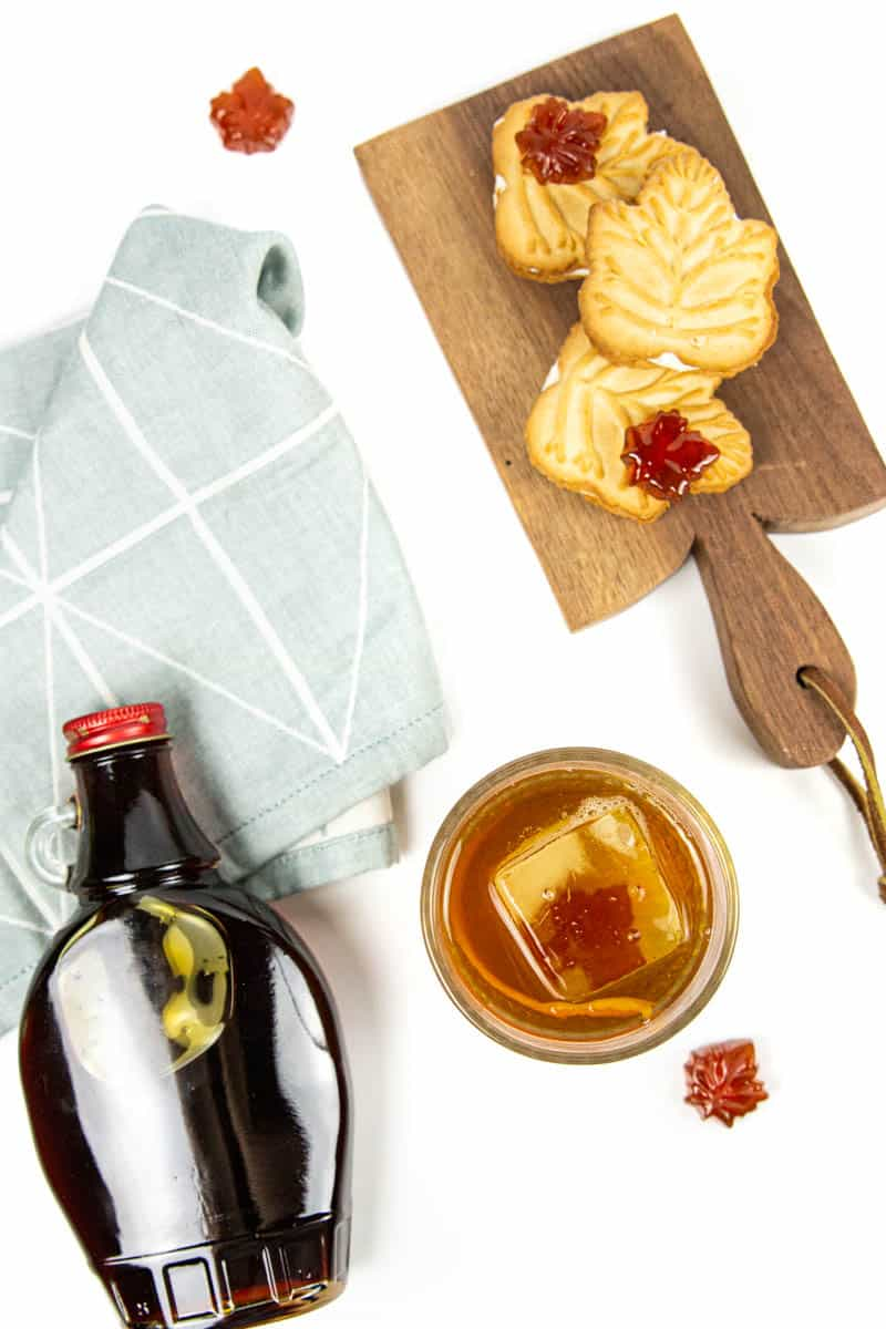 a bottle of maple syrup with a maple old-fashioned and a tray of maple cookies
