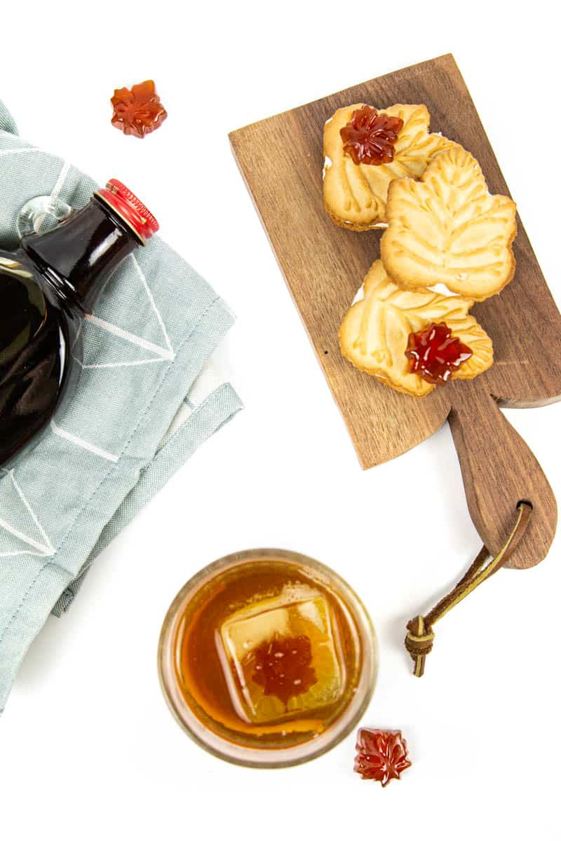 top view of a maple old-fashioned cocktail, a bottle of maple syrup and a tray of maple cookies