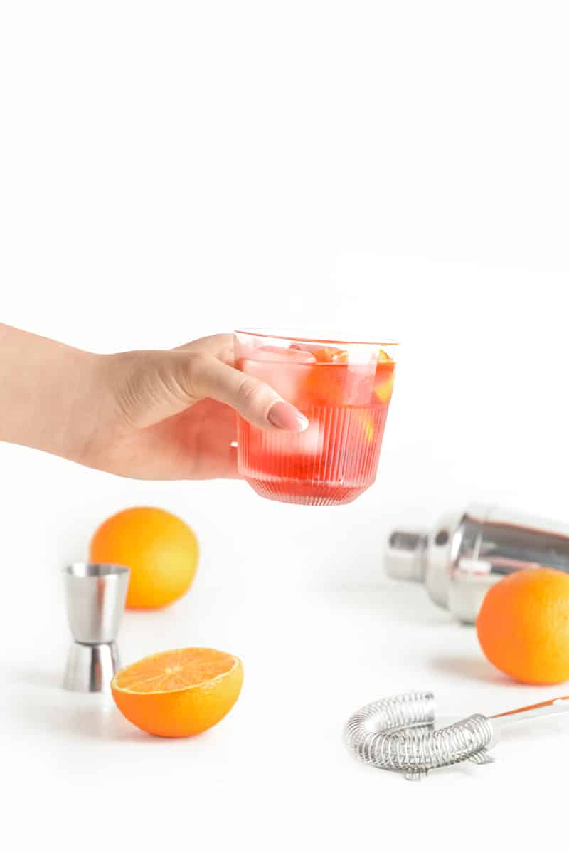 a hand holding a negroni cocktail over a white surface with oranges and a silver set containing a shaker, strainer and jigger