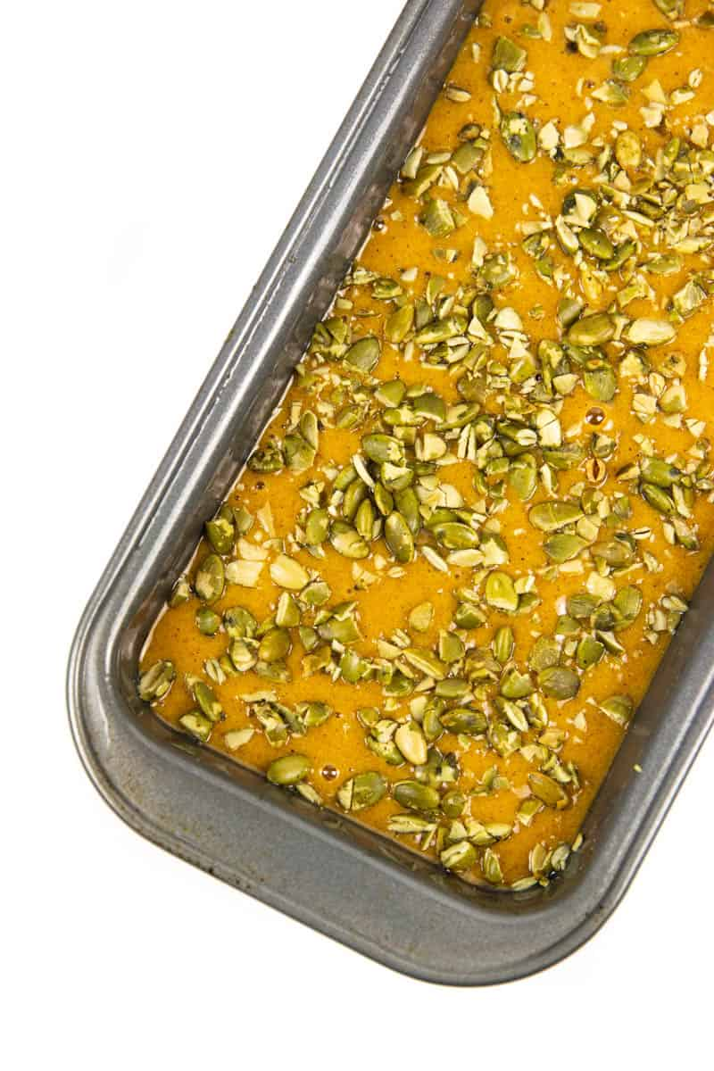 a loaf pan filled with easy pumpkin bread batter and topped with pumpkin seeds