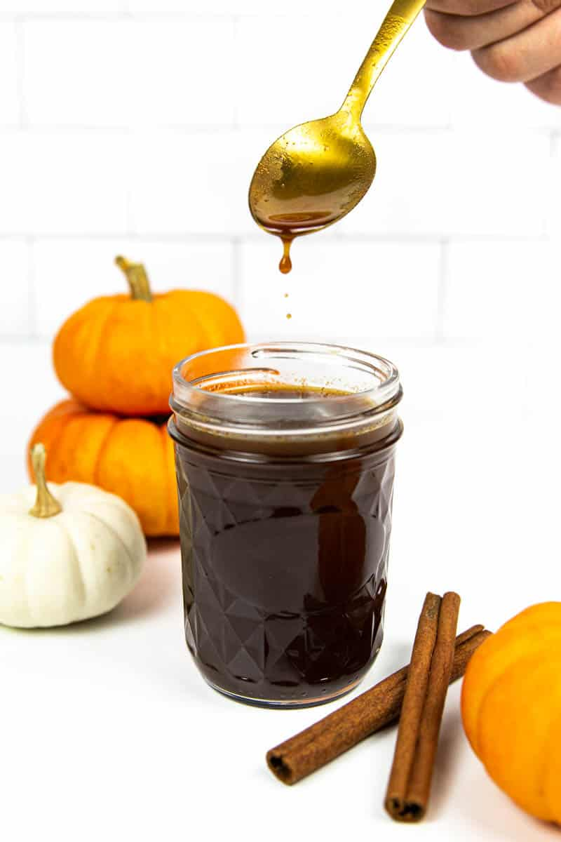 a hand holding a gold spoon dripping pumpkin spice syrup into a jar