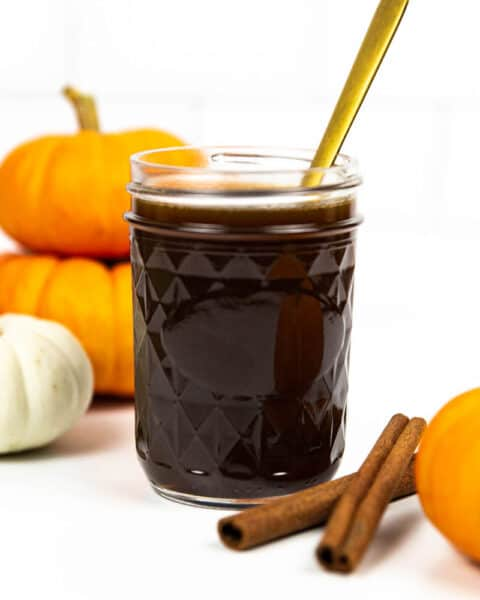 a gold spoon resting in a glass jar of pumpkin spice syrup