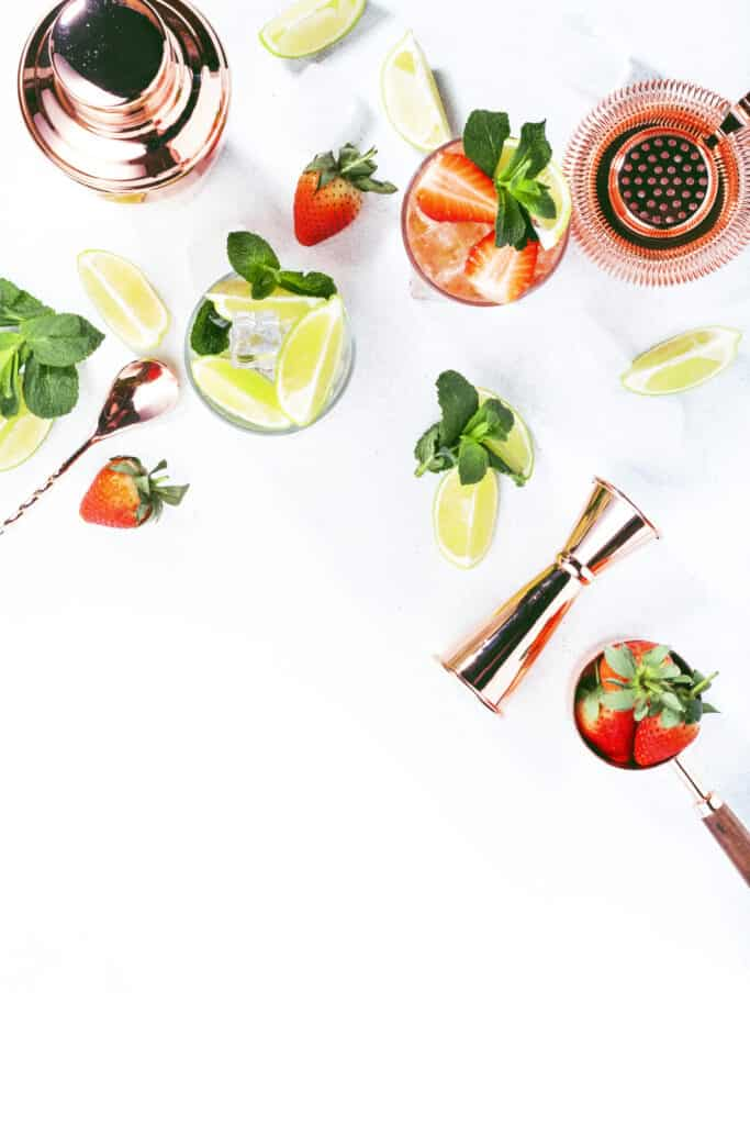 several cocktails with limes and strawberries next to copper bar tools on a white textured surface