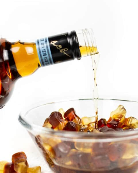 whiskey being poured into a clear glass bowl of cola gummy candy on a white background