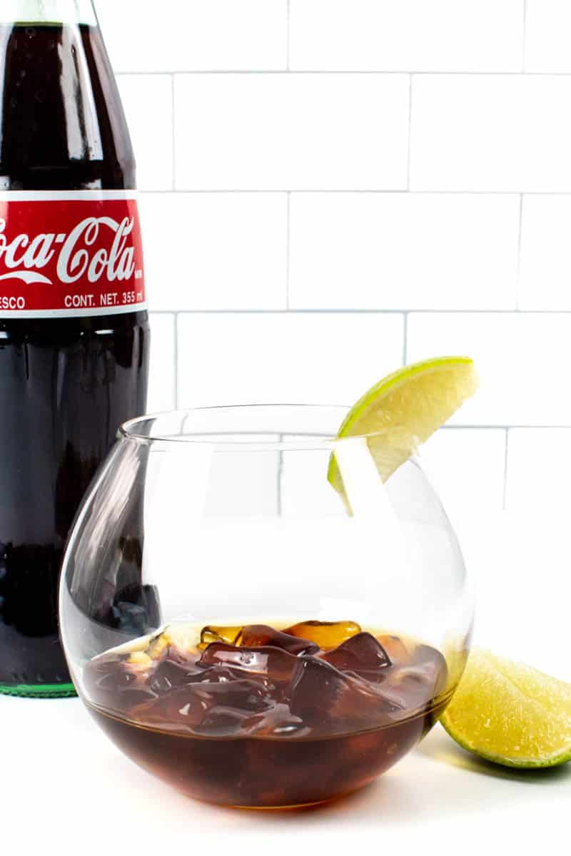 a bottle of coke next to a glass of whiskey and cola gummies garnished with a lime on a white tile background