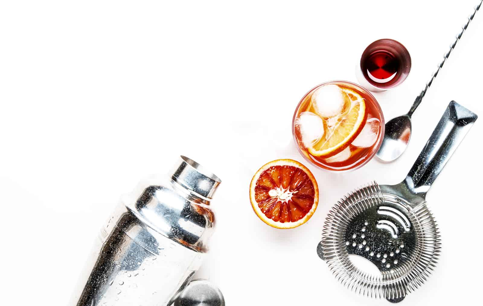 a top view of a silver cocktail shaker lying next to a cocktail strainer, bar spoon, orange and a cocktail on a white background