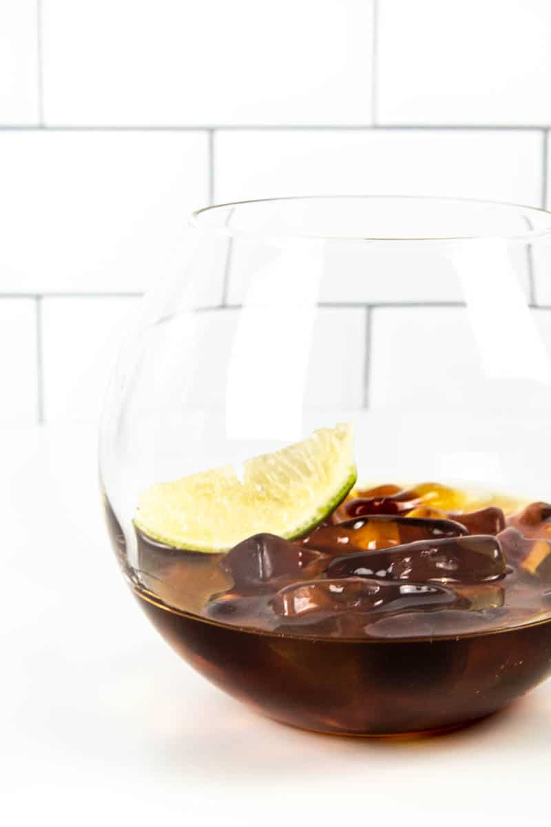 a cocktail glass filled with jack and coke gummies and a like wedge on a white tile background