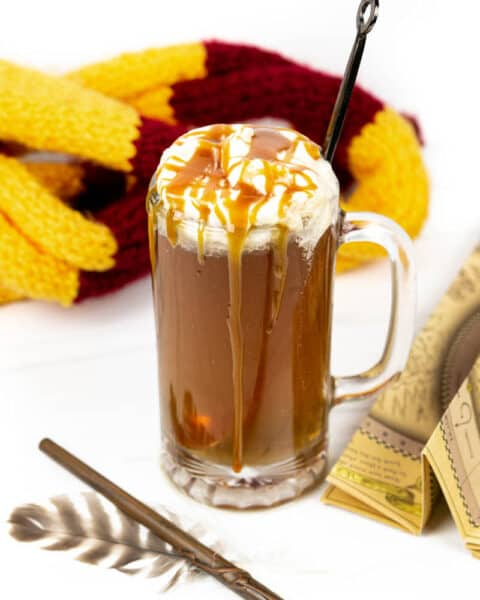 a clear mug of boozy Harry Potter butterbeer with whipped cream and butterscotch drizzle with a red and yellow scarf, map, wand and feather quill