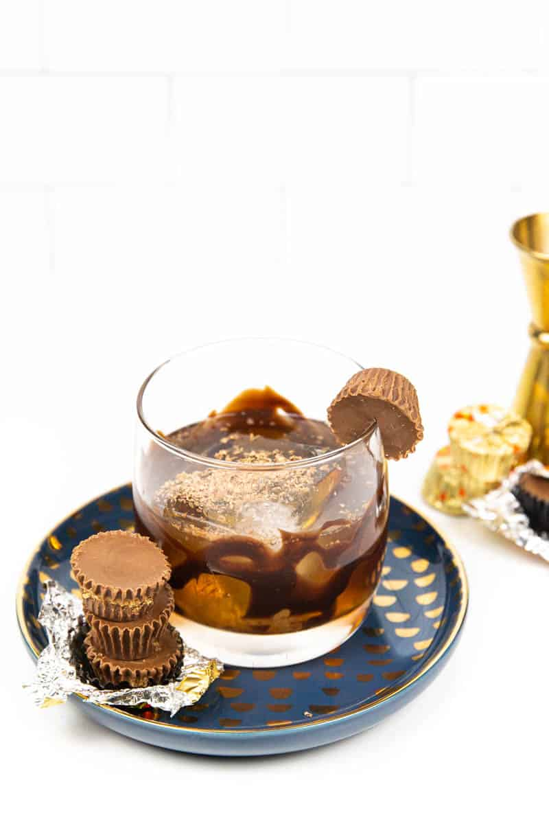 3 reese's cups on a plate with a peanut butter old-fashioned on a blue and gold plate next to candy wrappers and a gold jigger