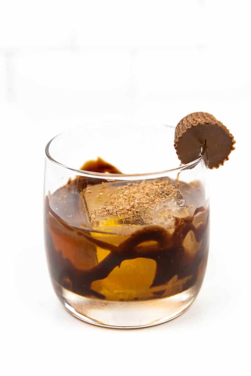 a peanut butter old-fashioned garnished with a peanut butter cup and a chocolate drizzle on a white background