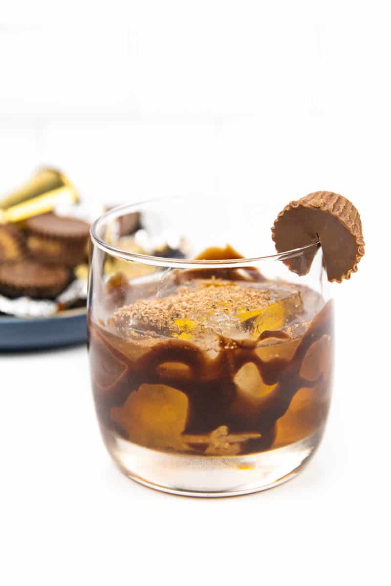 a peanut butter old-fashioned on a white background with a blue plate of peanut butter cup candies in the background