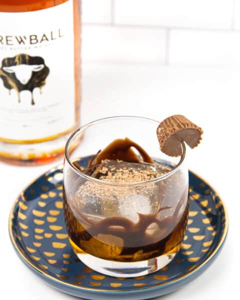 a peanut butter old-fashioned on a blue and gold plate with a bottle of skrewball whiskey