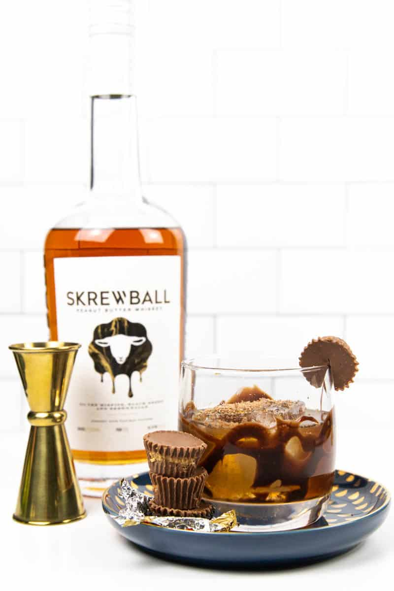 a peanut butter old-fashioned and 3 reese's cups on a blue plate with a bottle of skrewball and a gold jigger