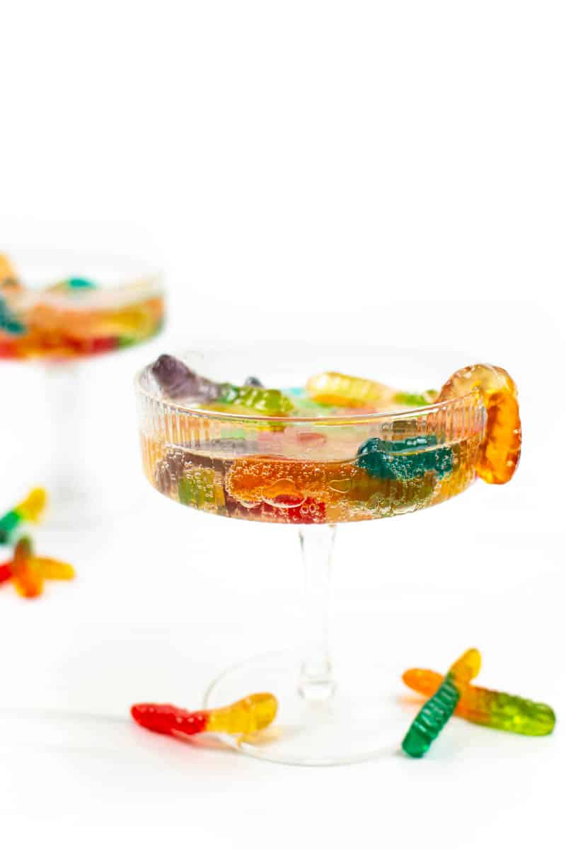 two couple glasses of vodka gummy worms on a white background