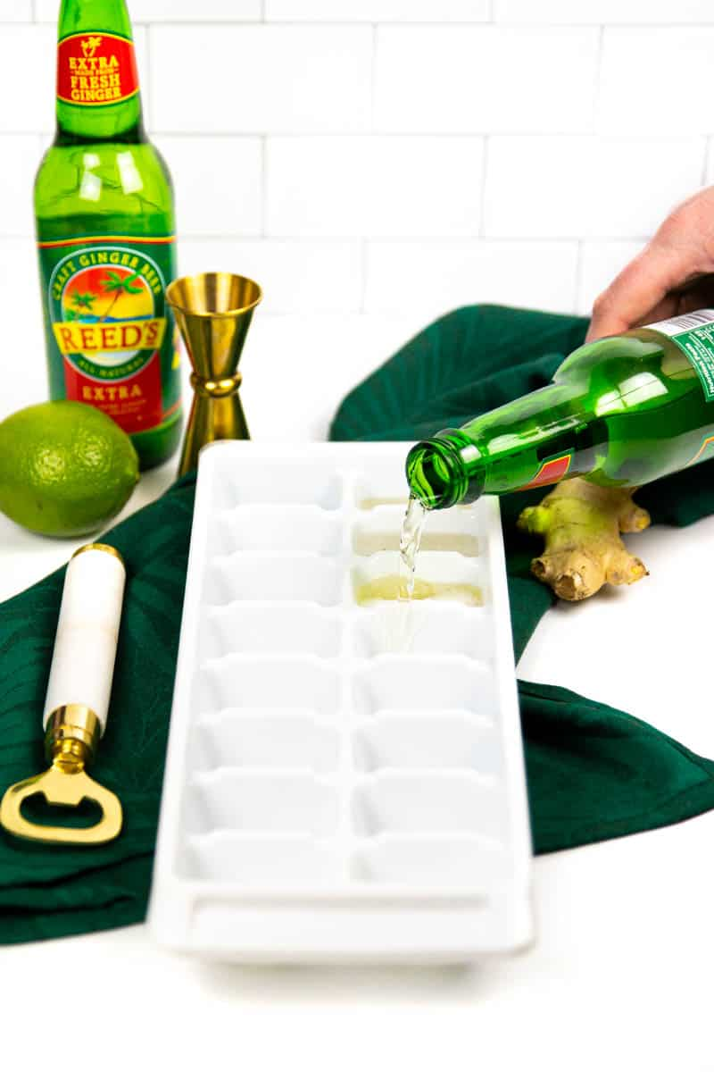 a hand pouring ginger beer into a white ice cube tray