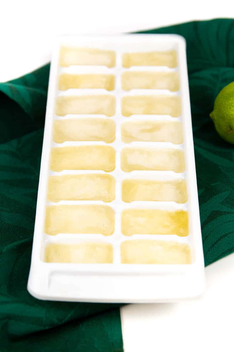 a tray of frozen ginger beer ice cubes on a green kitchen towel