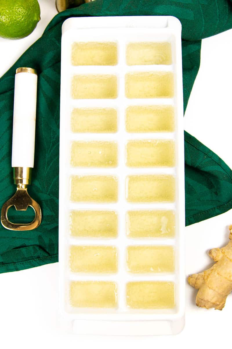 a tray of ready-to-freeze ginger beer ice cubes on a green kitchen towel