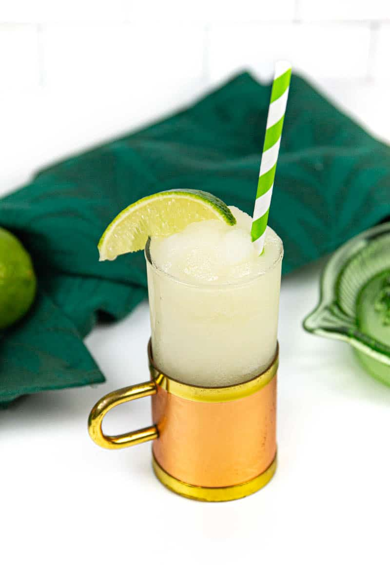a frozen Moscow mule in a copper and glass mug with a green and white striped paper straw and a wedge of lime on a white background with a green glass citrus squeezer and a green kitchen towel